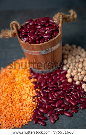 Red lentils , chickpeas and red beans are scattered from the basket on a black table - stock photo