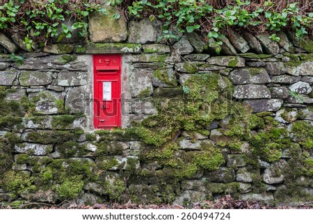 Red letterbox in dry stone wall - stock photo