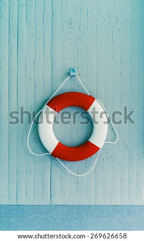 Red life buoy hanging on a blue wall. Help and support concept.(filtered) - stock photo