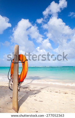 Red life buoy hanging on wooden pole, empty sandy beach of Dominican republic