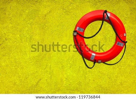 Red life buoy on the green plastered wall background - stock photo