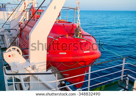 Red lifeboat on a cruise ship at sunset - stock photo