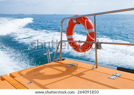 Red lifebuoy hanging on railings of fast safety rescue boat - stock photo