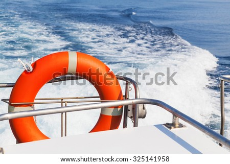 Red lifebuoy hanging on stern of fast safety rescue boat - stock photo