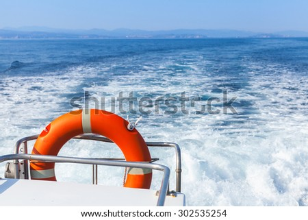 Red lifebuoy hanging on stern railings of fast safety rescue boat - stock photo
