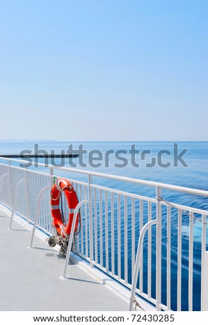 Red Lifebuoy in front of the blue sea and the white ship - stock photo
