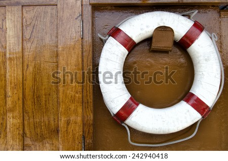 Red lifebuoy with rope on weathered wooden wall in port - stock photo