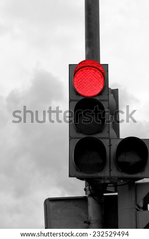 red light is photographed close up against a gray sky
