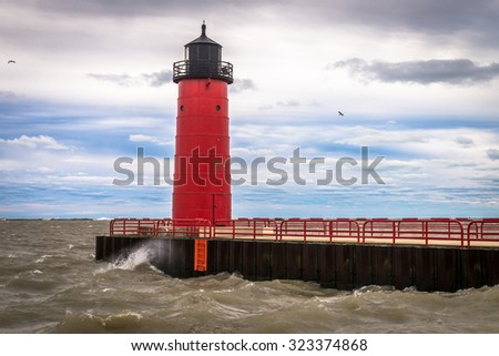 Red lighthouse against cloudy blue sky on Lake Michigan in Milwaukee, Wisconsin - stock photo