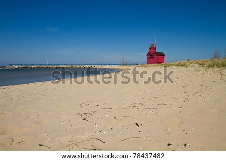 Red lighthouse along the beach of Lake Michigan - stock photo