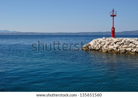Red lighthouse in port with stones. Podgora, Croatia. Space in left side. - stock photo