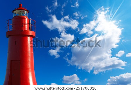 Red Lighthouse - La Spezia Italy. Red metallic lighthouse in the La Spezia harbor, Liguria, Italy. On blue sky with clouds and sun rays - stock photo