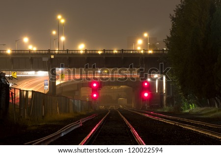 Red lights reflected on shiny train tracks with overpasses - stock photo