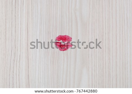 Red lipstick lips kiss print on wooden texture background