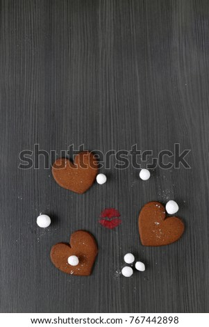 Red lipstick lips kiss print surrounded by sugar white balls and heart shaped brown cookies on black wooden texture background. Sweet valentine day symbols