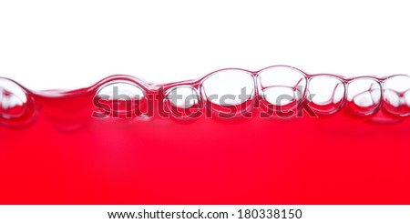 red liquid and bubble in front of white - stock photo