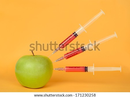 Red liquid in the syringe injected into green apple on a yellow background - stock photo