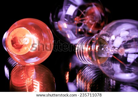 red lit lightbulb with two unlit purple ones - stock photo