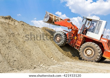 Red loader with wheels at earthmoving works. Bulldozer is pushing sand on huge pile. - stock photo