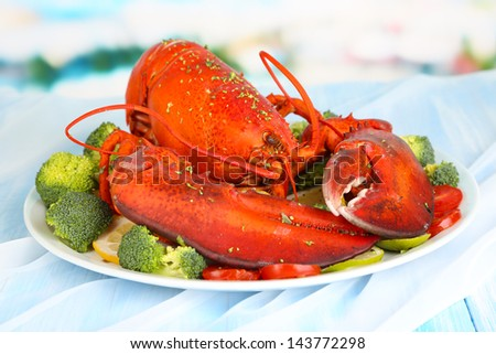 Red lobster on platter with vegetables on table close-up - stock photo
