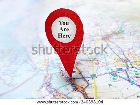 Red locator symbol on a map with You Are Here text                               - stock photo