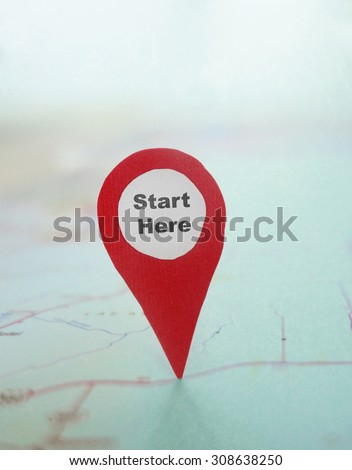 Red locator symbol with Start Here text on a map
