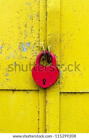 Red lock on a rusty yellow door - stock photo
