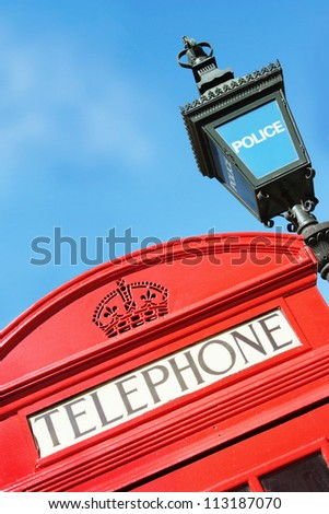Red London Phone Box and old-fashioned Police satation sign - stock photo