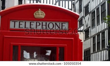 red London telephone box with Tudor house background - stock photo