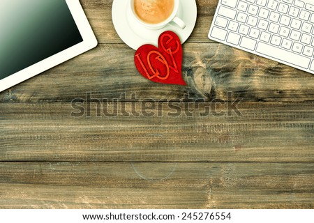 Red love heart, tablet pc, keyboard and coffee on wooden table. Valentines Day workplace. Retro style toned picture - stock photo