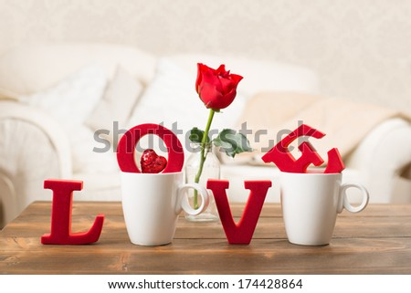 Red love letters in teacups with red rose in vase for Valentine's Day - stock photo