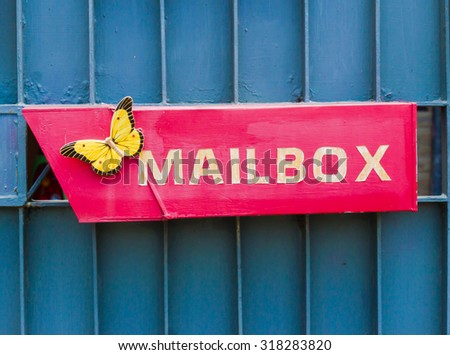 red mail box with yellow butterfly on blue background - stock photo