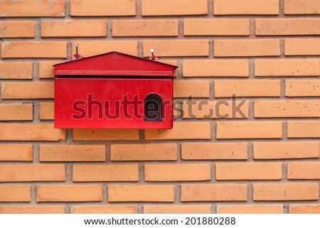 Red mailbox on a house wall - stock photo