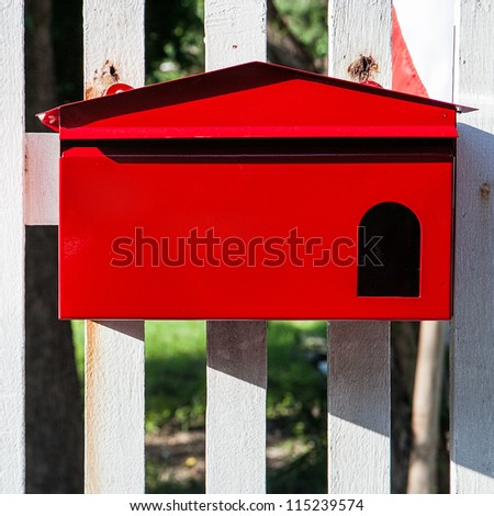 Red mailbox on white fence - stock photo