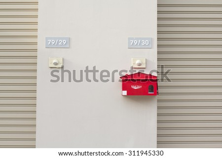 Red mailbox with white lettering on light brown  wall - stock photo