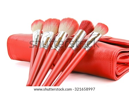 Red makeup brushes and leather bag on white background.
