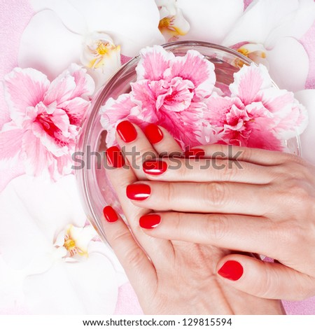 Red manicure with flowers - stock photo