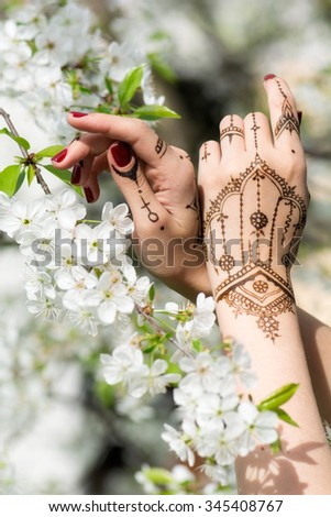 Red manicured hands with Mehndi in spring cherry blossom, Indian tradition. Vertical composition.