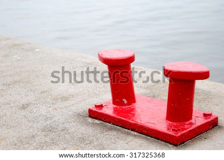 Red marine bollard on quayside - stock photo