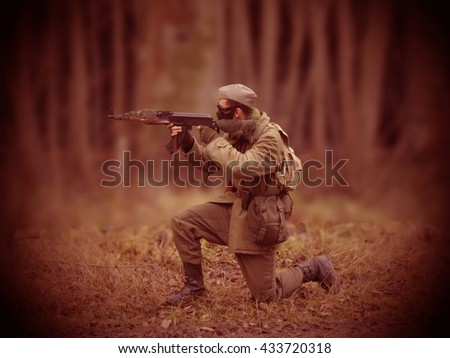Red Masked airsoft player, who plays for Russian side of the army, old time scenery, blurred blackground, dark vigneting - stock photo