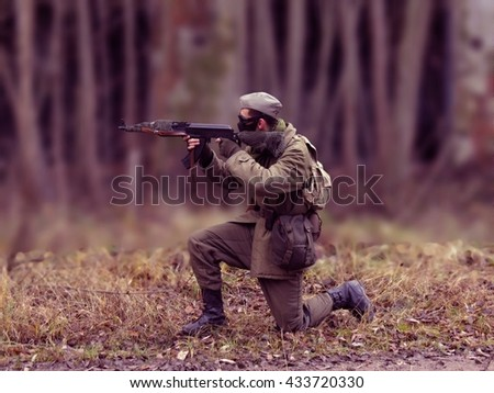 Red Masked airsoft player, who plays for Russian side of the army, old time scenery, blurred blackground - stock photo
