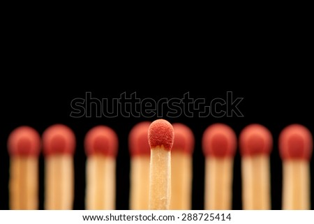 Red match standing in front of defocused set of eight red wooden matches, isolated on black background - stock photo