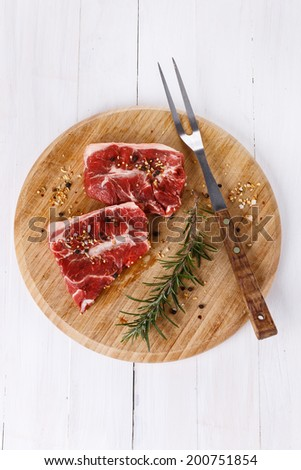 Red meat and rosemary over white wooden background. Top view - stock photo