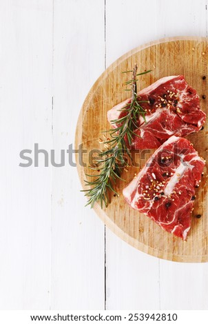Red meat and rosemary over white wooden background with copy space. Top view - stock photo