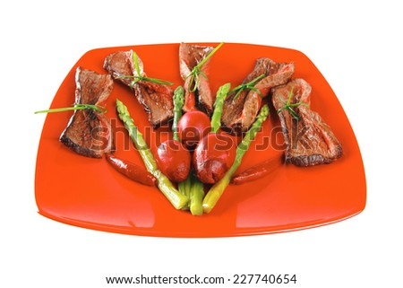 red meat slices and vegetables on red plate - stock photo