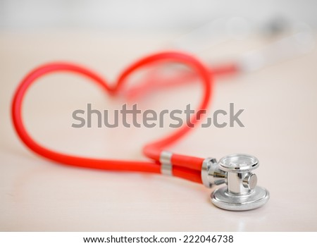 Red medical stethoscope in shape of heart  - stock photo