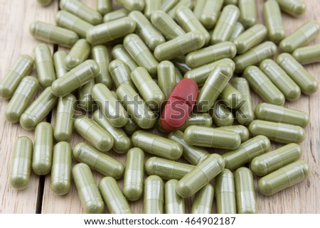 Red medicine pill around with herb capsule on wooden table, wood background.
