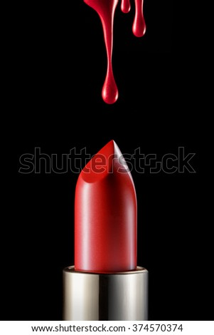 Red melting lipstick isolated on black background with drips on top - stock photo