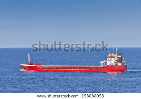 Red merchant ship in blue sea