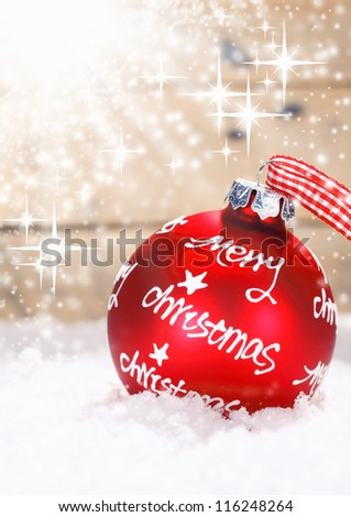 Red Merry Christmas bauble tied with a fresh red and white checked ribbon nestling in winter snow with twinkling stars of moisture lit by sun flare with copysapce - stock photo